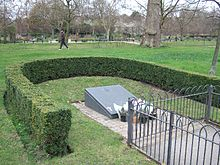 U-shaped hedge enclosure surrounding an oblong slate plaque on a wedge-shaped plinth, with flowers laid at the bottom