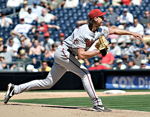 photo of major league baseball pitcher Randy Johnson on the mound, right after releasing a pitch to the plate, arm extended in front of him.