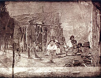 An old photograph depicting a group of poorly clad people in fronto of a small hut constructed of small tree branches