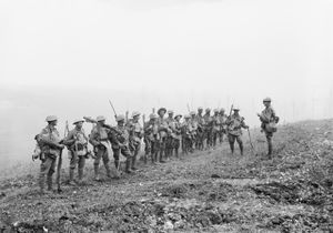 A line of soldiers in battle equipment face another soldier who is addressing them on a gentle slope.  Behind them, smoke or fog obscures the rest of the terrain.