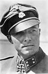A man wearing a military uniform, peaked cap and a neck order in the shape of a cross. His cap has an emblem in shape of a human skull and crossed bones.