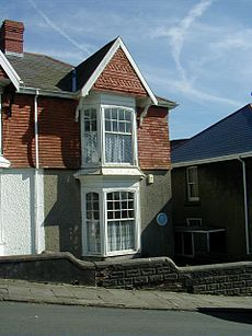On a hill street stands a two storied semi-detached house with bay windows to the front and a sloped tiled roof with a chimney.