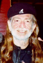 Head shot of Willie Nelson, with gray beard and long red hair and wearing a beret, smiles while looking at the camera.