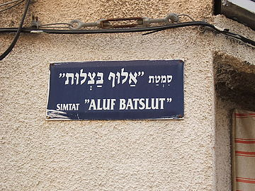 "Hebrew street sign, above in Hebrew alphabet, below in Latin transliteration. Aluf Batslut veAluf Shum(he) (""The Knight of Onions and the Knight of Garlic"") is a story by Hayim Nahman Bialik."