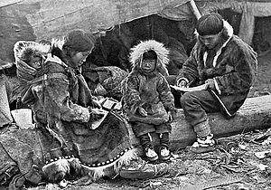 An Inuit family is sitting on a log outside their tent. The parents, wearing warm clothing made of animal skins, are engaged in domestic tasks. Between them sits a toddler, also in skin clothes, staring at the camera. On the mother's back is a baby in a papoose.