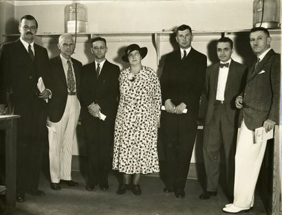 monochrome photograph of six men and a woman, standing