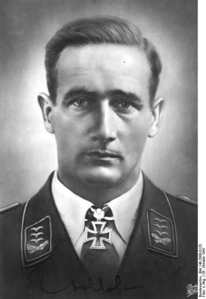 The head of a man, shown from the front. He wears a military uniform, a white shirt with an Iron Cross displayed at the front of his shirt collar. His hair appears dark and is combed back, his facial expression is a determined; his eyes are looking into the camera.