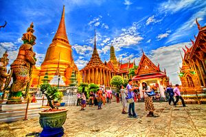 A Thai temple complex with several ornate buildings and a stupa, and a lot of visitors