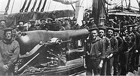 A group of twenty-six sailors posing around a rifled naval cannon.