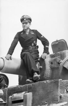 A man, wearing dress uniform and a cap, sits on top of a tank barrel